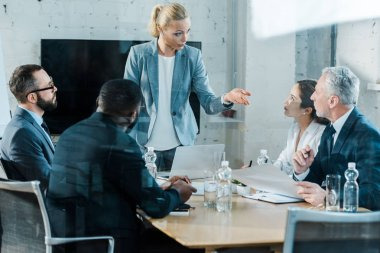 selective focus of business coach talking and gesturing in conference room near multicultural coworkers