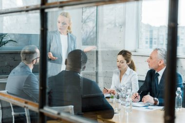 selective focus of business coach talking while gesturing in conference room near multicultural coworkers