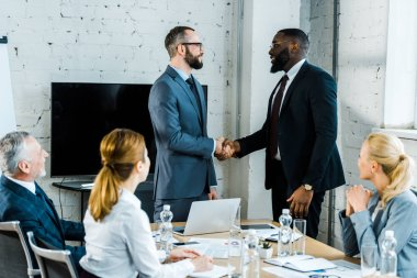 multicultural businessmen shaking hands near colleagues in conference room