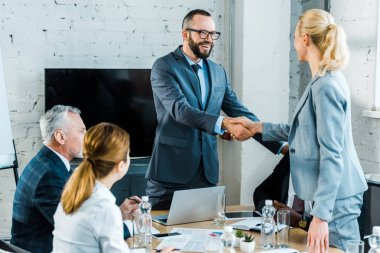 handsome business coach shaking hands with blonde woman near multicultural coworkers