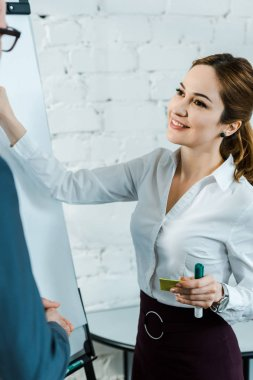 businesswoman standing near white board and looking at businessman