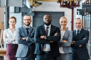 multicultural group of handsome businessmen and cheerful businesswomen standing with crossed arms and looking at camera
