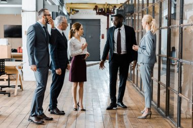 multicultural handsome businessmen and attractive businesswomen standing and talking in office