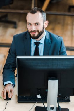 Cheerful bearded businessman looking at camera near computer monitor in office stock vector