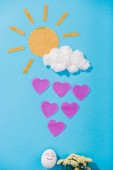 top view of paper sun, cotton candy cloud, egg with happy face expression, flowers and heart-shaped raindrops on blue