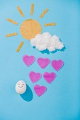 top view of paper sun, cotton candy cloud, egg with happy face expression and heart-shaped raindrops on blue