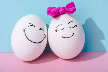 Egg with bow and egg with happy face expression on blue and pink stock vector