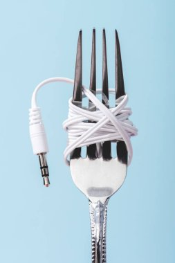 close up view of earphones wrapped over metal fork isolated on blue, music concept