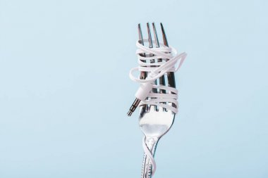 top view of earphones wrapped over metal fork isolated on blue with copy space, music concept