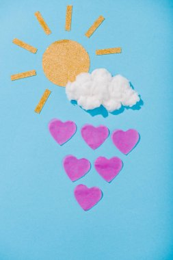 Top view of paper sun, cotton candy cloud and heart-shaped raindrops on blue stock vector
