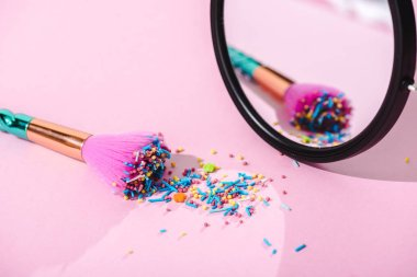 makeup brush covered in colorful sprinkles with reflection in mirror on pink