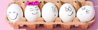 panoramic shot of eggs with different face expressions in egg carton on pink