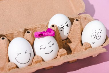 Eggs with various face expressions in egg carton on pink stock vector