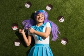 Asian anime girl in purple wig with emoticons lying on grass