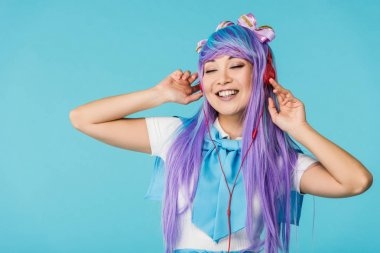 Smiling anime girl in purple wig listening music in headphones isolated on blue
