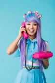 Ázsiai lány beszélget a telefonon izolált kék