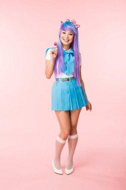 Full length view of smiling asian otaku girl holding lollipop on pink stock vector