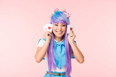 Happy asian anime girl in purple wig holding cards with hearts isolated on pink stock vector