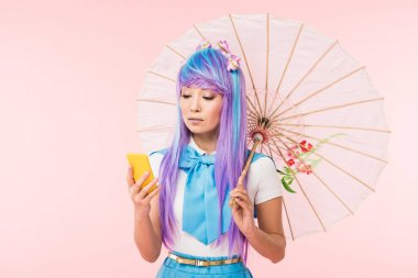 Asian anime girl holding paper umbrella and using smartphone isolated on pink