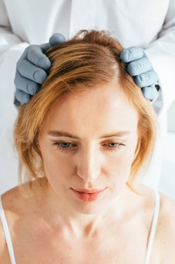 cropped view of dermatologist in latex gloves examining hair of patient