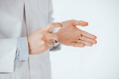 cropped view of doctor applying antibacterial spray on hand isolated on white