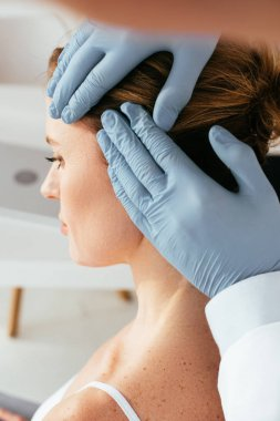 cropped view of dermatologist in latex gloves examining hair of patient in clinic