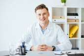 Fotografia medico allegro e bello in camice bianco seduto con le mani serrate in clinica