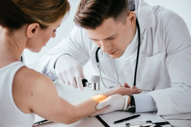 selective focus of dermatologist examining hand of woman with dermatoscope