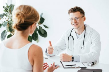 selective focus of cheerful doctor in glasses showing thumb up while looking at patient