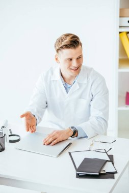 Cheerful doctor in white coat gesturing near laptop in clinic stock vector