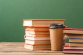 Knihy a šálek na jedno použití na dřevěné ploše na zelené