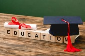 wooden blocks with letters, academic cap and diploma on wooden surface isolated on green