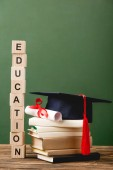 Fotografie wooden blocks with letters, books, academic cap and diploma on wooden surface isolated on green