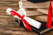 diploma with ribbon and stack of books on wooden surface
