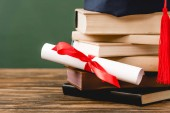 books, academic cap and diploma on wooden surface isolated on green