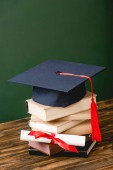 books, academic cap and diploma on wooden surface on green