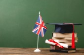 Books, academic cap, diploma and british flag on wooden surface isolated on green