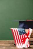 books, academic cap, diploma and american flag on wooden surface isolated on green