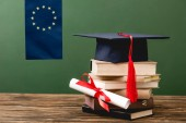 european flag, stack of books, diploma and academic cap on wooden surface isolated on green