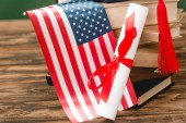 books, diploma and american flag on wooden surface