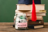 Fényképek könyvek, akadémiai sapka és malacka bank fa felületre izolált zöld