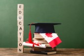 Photo wooden blocks with letters, diploma, books, academic cap and canadian flag on wooden surface isolated on green