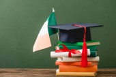 Fotografie books, diploma, academic cap and irish flag on wooden surface isolated on green