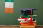 books, diploma, academic cap and irish flag on wooden surface isolated on green
