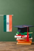 books, diploma, academic cap and indian flag on wooden surface isolated on green