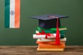 könyvek, oklevéllel, akadémiai sapkával és indiai zászlóval a zöld felületre izolált fa felületen
