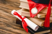 Photo academic cap, books, medal and diploma on wooden surface