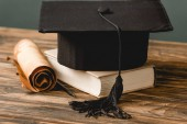 book, academic cap and scroll on wooden surface isolated on grey