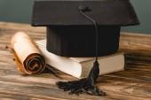 kniha, akademická čepice a rolování na dřevěné ploše izolované na šedé