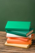 stack of colorful books on wooden surface isolated on green